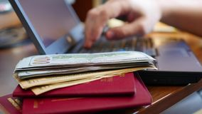 Overhandigt het typen tekst op laptop, close-up van geld en paspoorten stock videobeelden