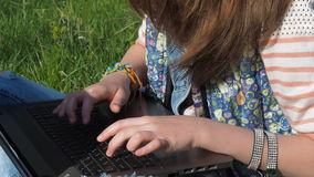 Overhandigt het typen tekst op laptop Het meisje in het park typt op laptop De haveloze jeans en dient armbanden in stock footage