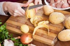 Overhandigt schoonmakende aardappels Stock Afbeelding