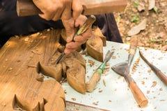 Overhandigt woodcarver terwijl het werken met de hulpmiddelen Stock Afbeelding