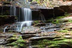 Overhangend gedeelte van natte die rotsen in mos en de herfstbladeren, waterval het draperen worden behandeld stock foto's