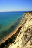 Overhanging clay rock on turquoise sea Stock Photography