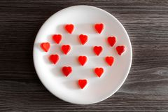 Overhead above top close up view photo of yummy tasty cute gummy red small little tiny hearts in on round white plate on kitchen s. Urface table wooden desk Stock Photo