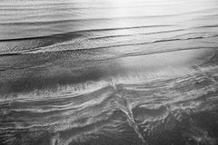 Overhead aerial shot of waves breaking on a beach. Black and white abstract shot of waves breaking on a beach Stock Photo