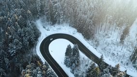 Overhead aerial top view over car travelling on hairpin bend turn road in mountain winter snow covered forest. White. Pine tree woods. Snowy street path stock video