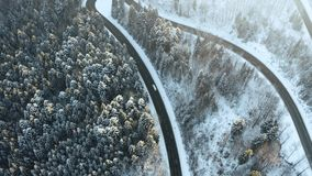 Overhead aerial top view over car travelling on hairpin bend turn road in mountain winter snow covered forest. White. Pine tree woods. Snowy street path stock video footage