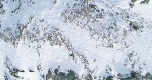 Overhead aerial top view over winter snowy mountain rocks.Rocky mountains covered in snow and ice glacier.Winter wild