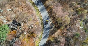 Overhead aerial top view over yellow vintage car travelling on road in colorful autumn forest.Fall orange,green tree. Overhead aerial top view over yellow car stock video footage