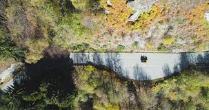 Overhead aerial top view over yellow vintage car travelling on road in colorful autumn forest.Fall orange,green tree. Overhead aerial top view over yellow car stock footage