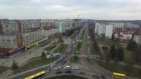 Overhead aerial view of cars driving around circle road in city street. Cloudy day stock video footage