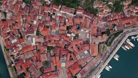 Overhead aerial view of rooftops and streets in historic old town of Kotor and Dobrota and bay for liner and boats in. Montenegro stock video