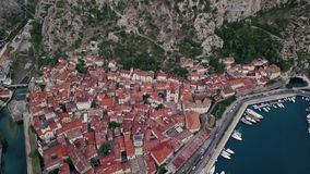 Overhead aerial view of rooftops and streets in historic old town of Kotor and Dobrota and bay for liner and boats in. Montenegro stock footage