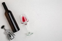 Overhead angled view of a large bottle of red wine, drinking glass on white background Stock Photo
