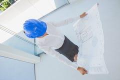 Overhead of an architect holding a blueprint Royalty Free Stock Photos