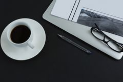 Black coffee, spectacles, pen, laptop and newspaper on black background Stock Photos