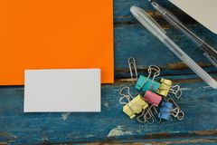 Book, paper clip, visiting cards and blank paper on wooden plank Stock Image