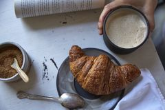 Overhead breakfast scene. Overhead view of a woman sipping a latte, eating a croissant, and reading a book in the morning at a white table Royalty Free Stock Photography