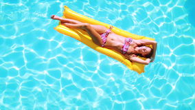 Overhead of brunette lying on lilo in pool on sunny day stock video