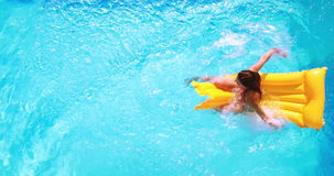 Overhead of brunette sitting on lilo in pool on sunny day stock video