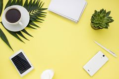 Overhead business frame with a solar battery, phone and cup of coffee. Top view royalty free stock photos
