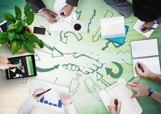 Overhead of business team with green wood panel and arrow with handshake doodles. Digital composite of Overhead of business team with green wood panel and arrow Stock Photos