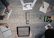 Overhead of business team with grey wood panel and idea doodle. Digital composite of Overhead of business team with grey wood panel and idea doodle Royalty Free Stock Photo