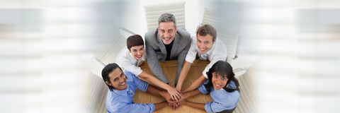 Overhead of business team looking up and putting hands together at table and blurry white transition Stock Photos