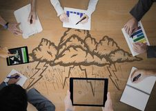 Overhead of business team with wood panel and storm cloud doodle. Digital composite of Overhead of business team with wood panel and storm cloud doodle Royalty Free Stock Photos
