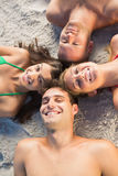 Overhead of cheerful friends lying together in a circle. On the beach Stock Photography
