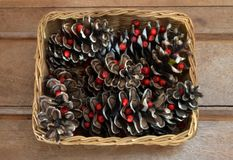 Close up of group of pine cones, with dried red berries. in wicker basket on wood table stock images