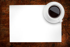 Overhead coffee. A cup of coffee over head on white paper with wood background Royalty Free Stock Photography
