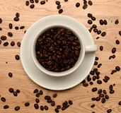Overhead coffee cup filled with beans Royalty Free Stock Photography