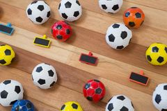 Colorful footballs on wooden table Royalty Free Stock Photography