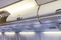 Overhead compartment - detail of an airplane cabin interior. Overhead compartment closed and opened - detail of an commertial airplane cabin interior royalty free stock photo