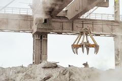 Overhead crane with mechanical multivalve clamshell grab in hot outdoors industrial plant shop. Heavy industry royalty free stock image