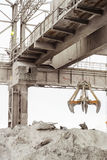 Overhead crane with mechanical multivalve clamshell grab in outdoors industrial plant shop. Heavy industry stock photos