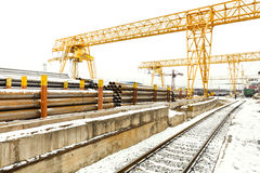 Overhead cranes over railroad in outdoor warehouse Stock Photos