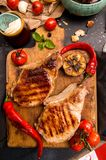 Overhead of dinner table. Delicious grilled barbecue pork meat o. N old wooden cutting board. Picnic bbq party concept. Top view Royalty Free Stock Images