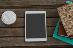 Disposable glass, books and digital tablet on wooden plank Stock Images