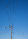 Overhead electicity lines and lampost. Overhead electricity lines with street light and lamp post against a clear, blue sky royalty free stock photos