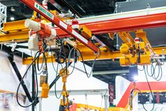 Overhead electric chain hoist with hook and remote switch control. For industrial stock photos