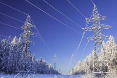 The overhead electric line over blue sky. Electrical wires of power line or electrical transmission line covered by sno. W in the winter forest stock photography