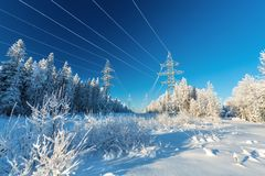 The overhead electric line over blue sky.  Electrical wires of power line or electrical transmission line. Covered by snow in the winter forest Stock Photo