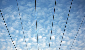 Overhead electrical wires. Electrical wires with beautiful cloudy sky royalty free stock photo