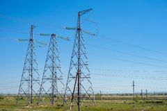 Overhead electricity transmission lines in the summer, against the background of the blue sky. . Metallic supports of overhead power lines on background blue Stock Photo