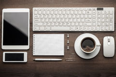 Overhead of essential office objects in order. On wooden desk Royalty Free Stock Photography