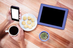 Overhead of feminine hands holding smartphone and coffee Royalty Free Stock Photo