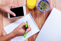 Overhead of feminine hands holding smartphone and taking notes Stock Photos