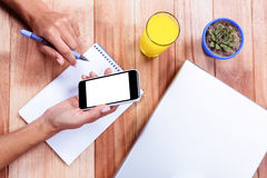 Overhead of feminine hands holding smartphone and taking notes Royalty Free Stock Image