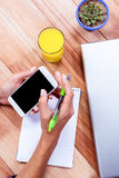 Overhead of feminine hands holding smartphone and taking notes Royalty Free Stock Images
